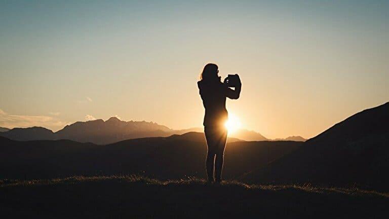 夕日の写真を撮る女性