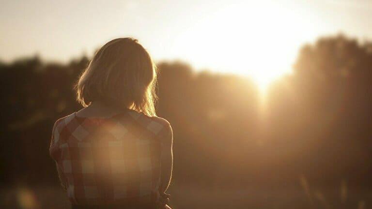 夕陽を見て考える女性